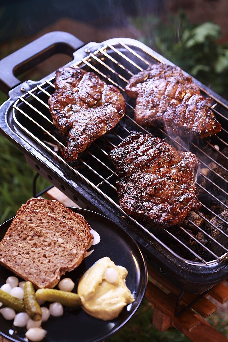 Pork neck steaks on a barbecue