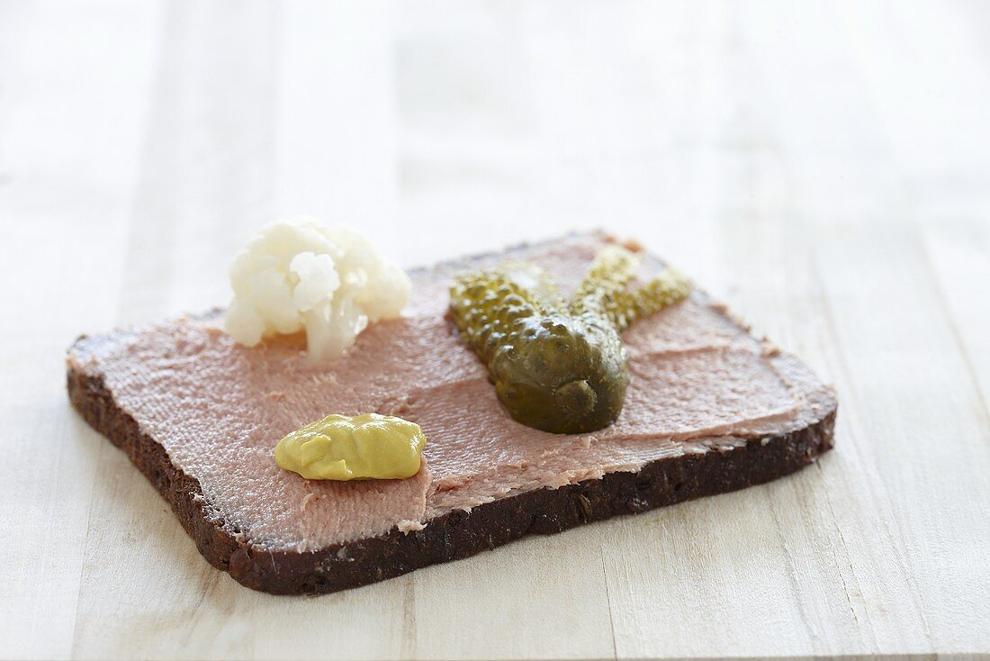 Liver sausage spread on a slice of bread with mustard and a gherkin