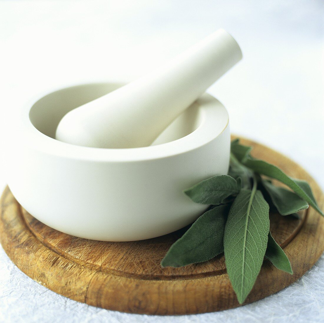 Stone mortar and pestle on a kitchen board with sage