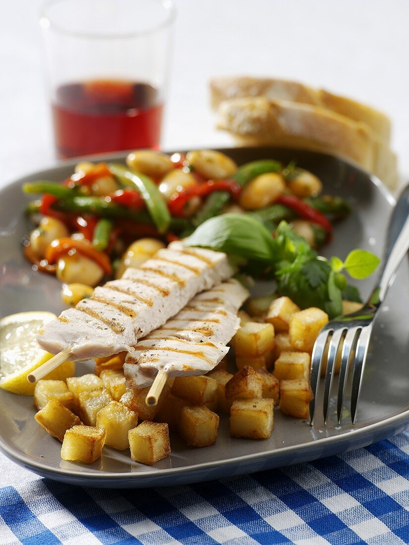 Chicken kebab with diced potatoes and bean salad