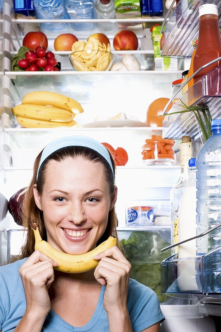Young woman with banana in front of open fridge