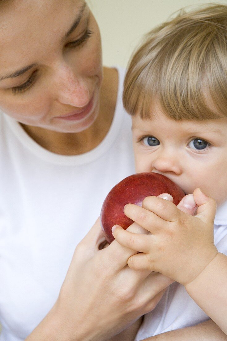 Small child biting into an apple her mother is holding