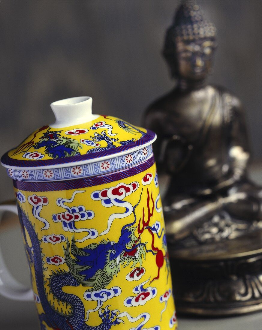 Decorated teacup with lid in front of statue of Buddha