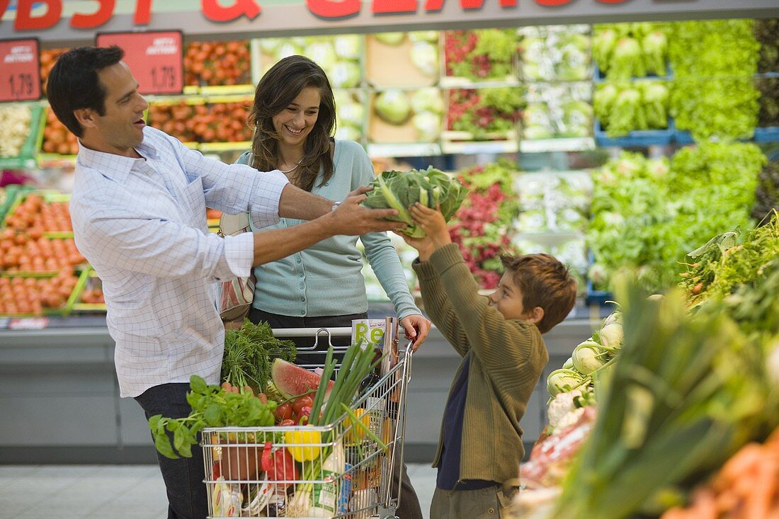 Father and son having fun at supermarket vegetable counter