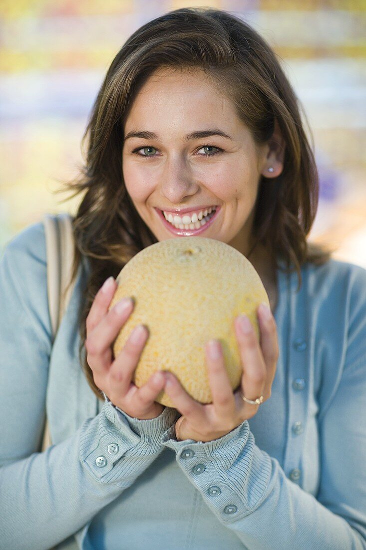 Young woman holding a netted melon in her hands