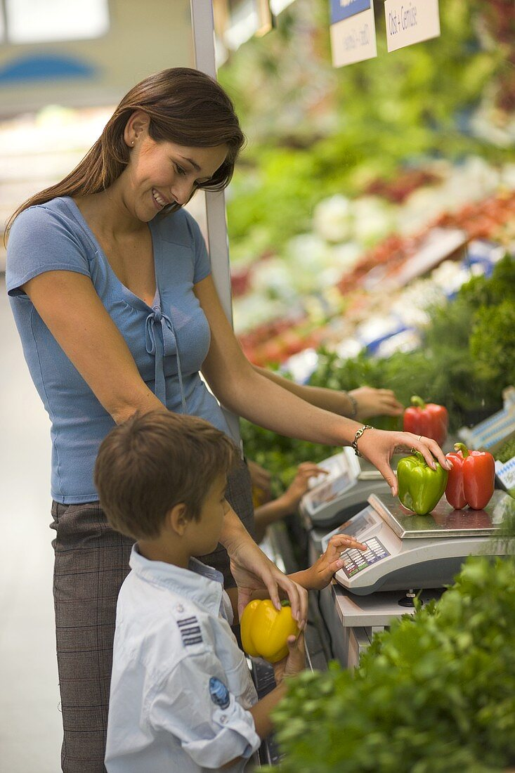 Mother and son weighing vegetables in a supermarket