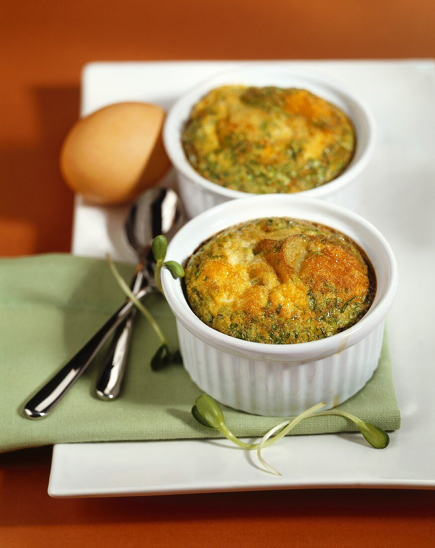 Egg soufflés with herbs in soufflé dishes