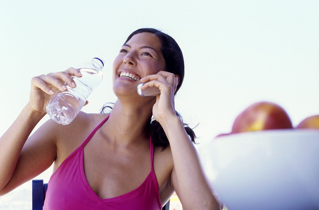 Young woman with mobile phone and bottle of water