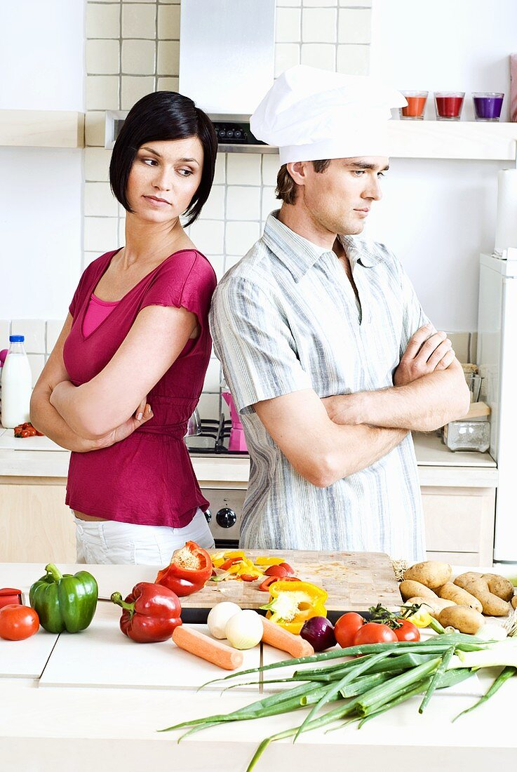 Discord in the kitchen: man & woman with their backs to each other