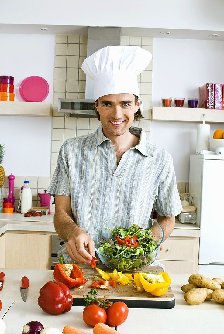 Man in chef's hat preparing salad