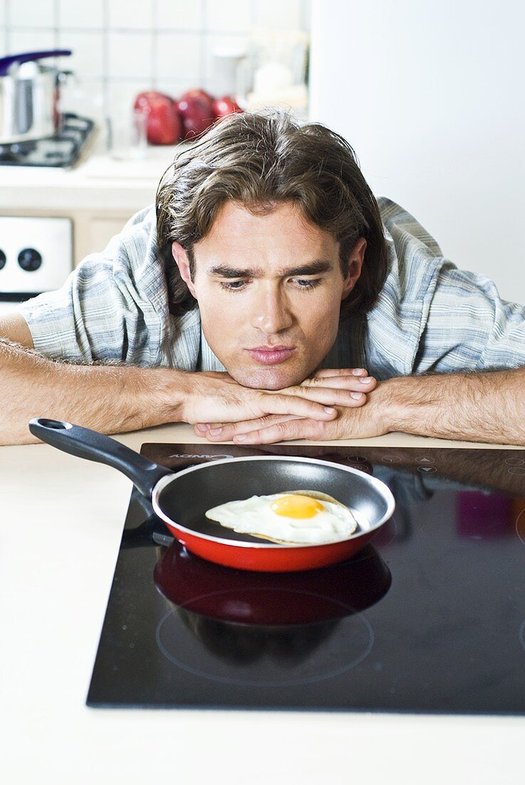 Man looking at a fried egg