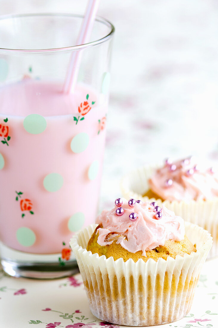 Fairy cakes with pink icing and a strawberry milkshake