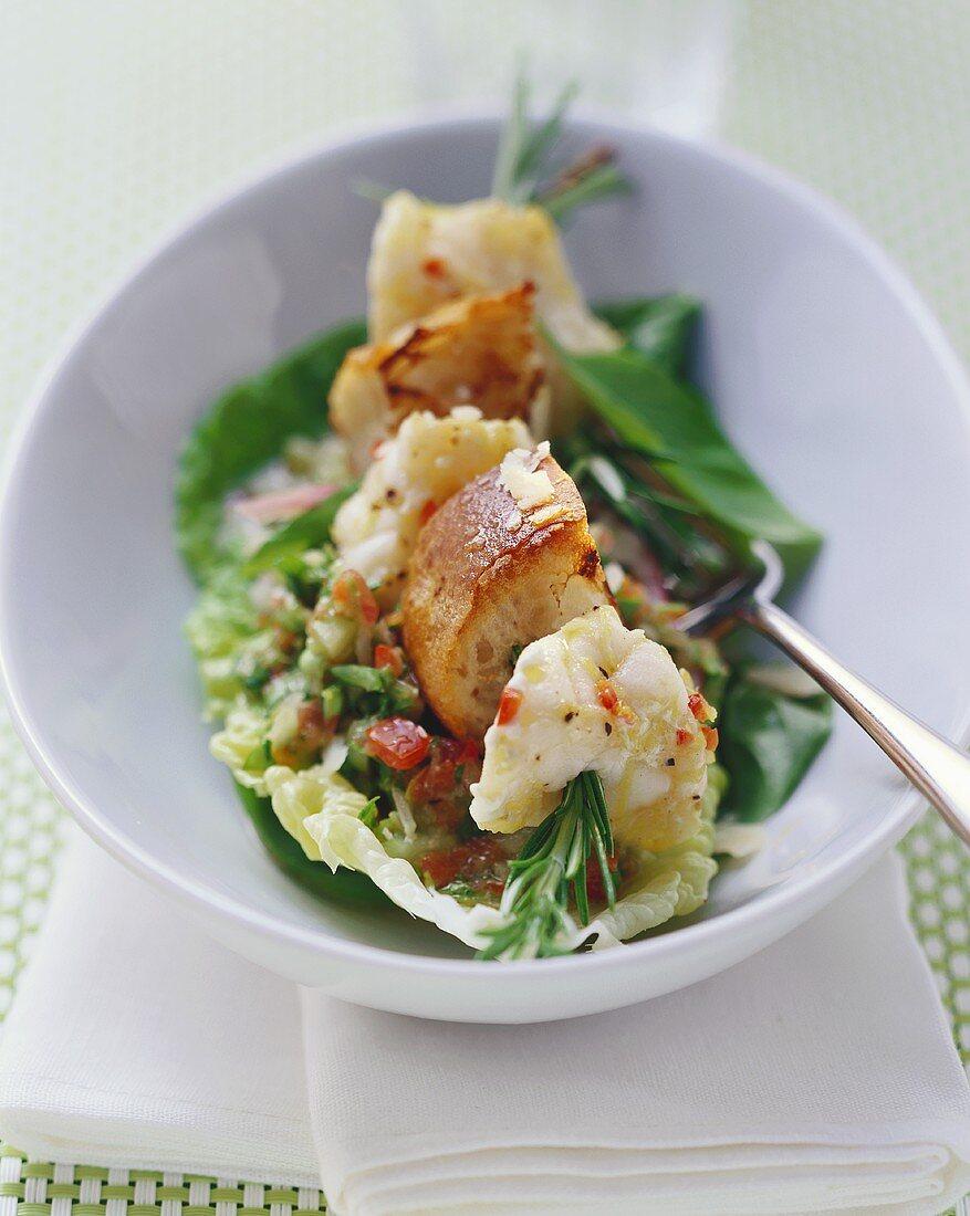 Monkfish skewered on rosemary on salad