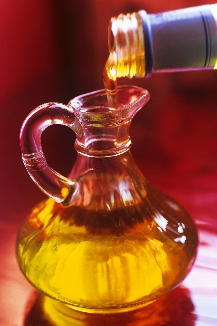 Pouring olive oil from bottle into carafe