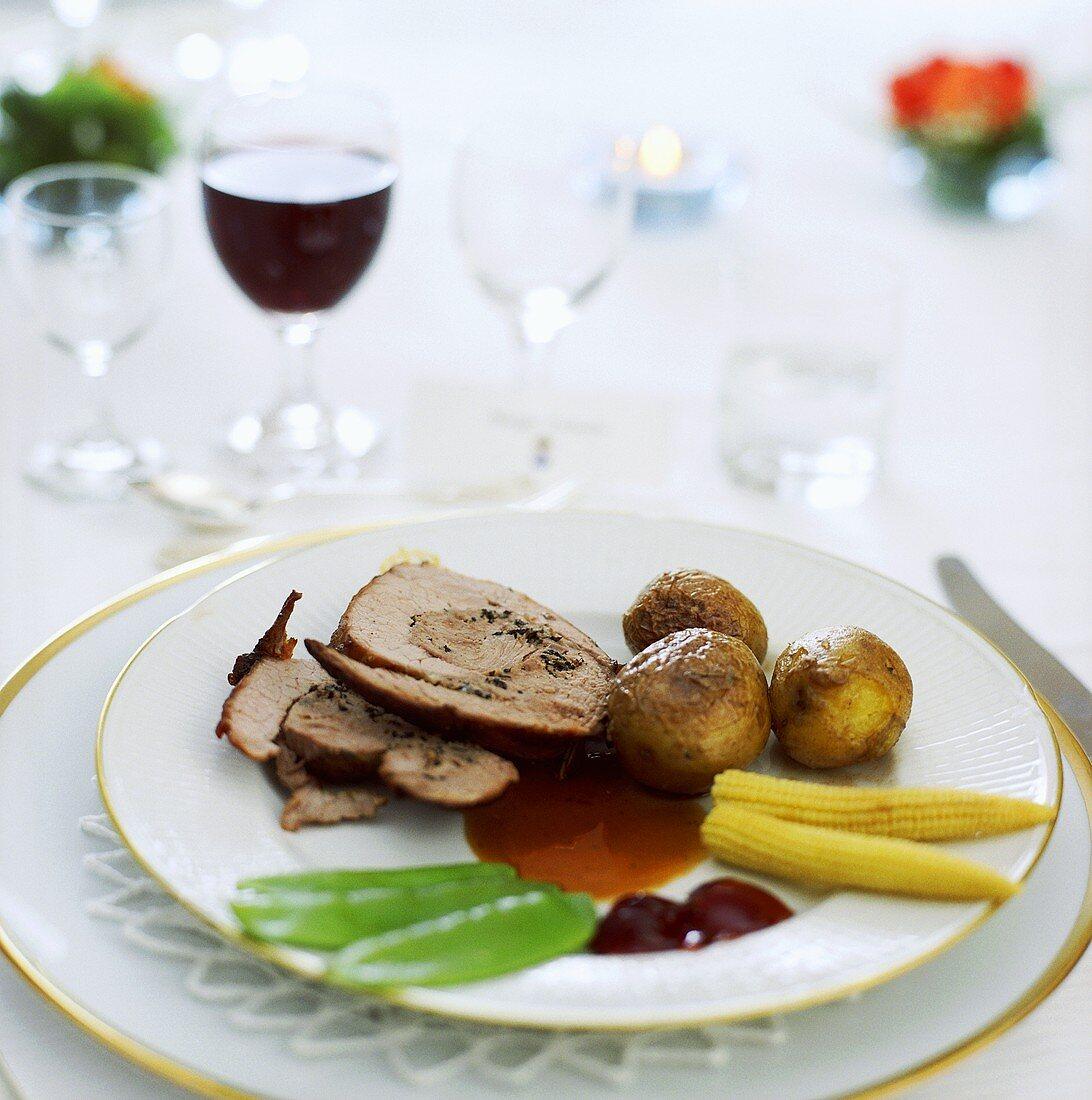 Rolled veal roast with vegetables on elegant tableware