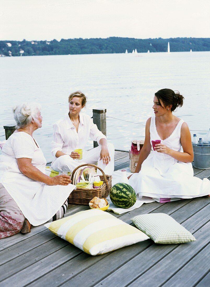 Three women picnicking by a lake