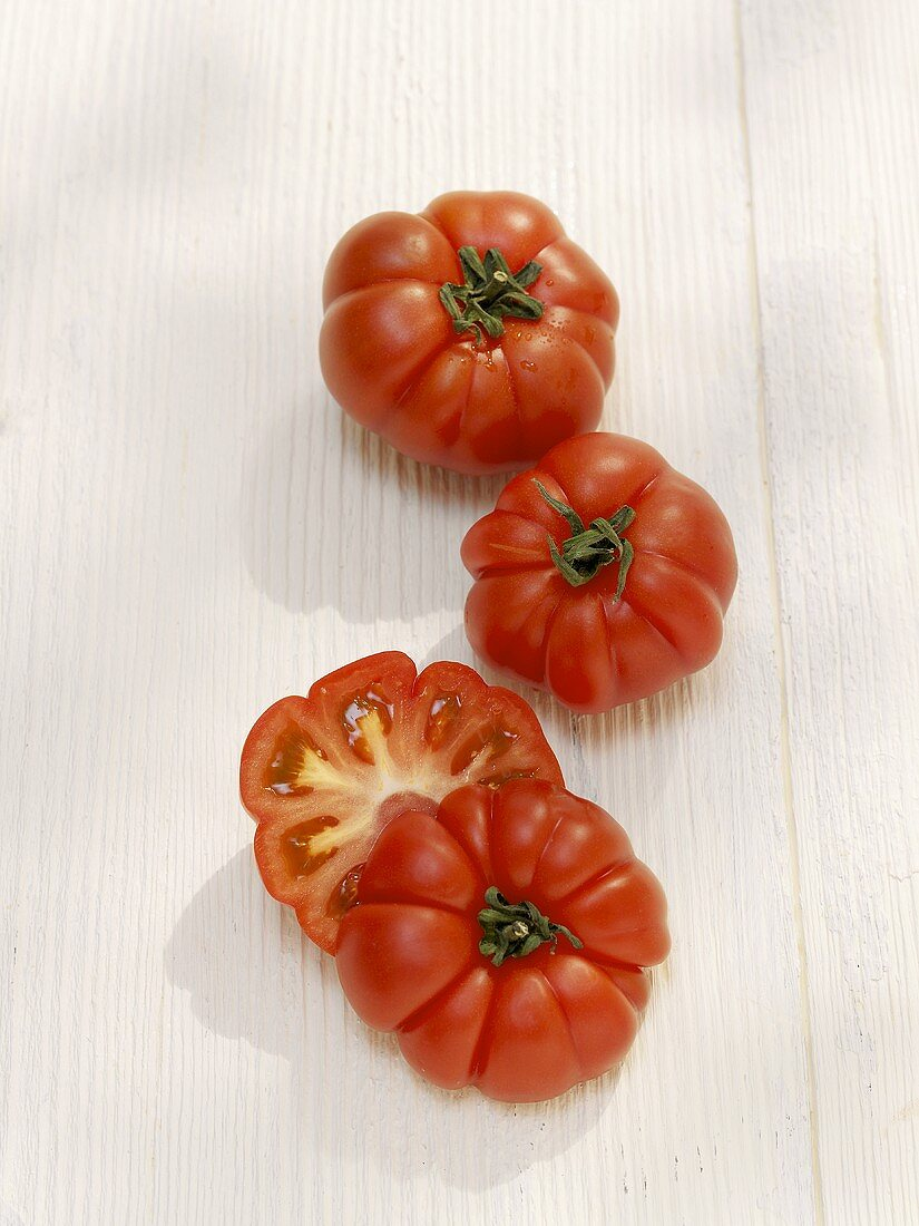 Two whole and one halved beefsteak tomato