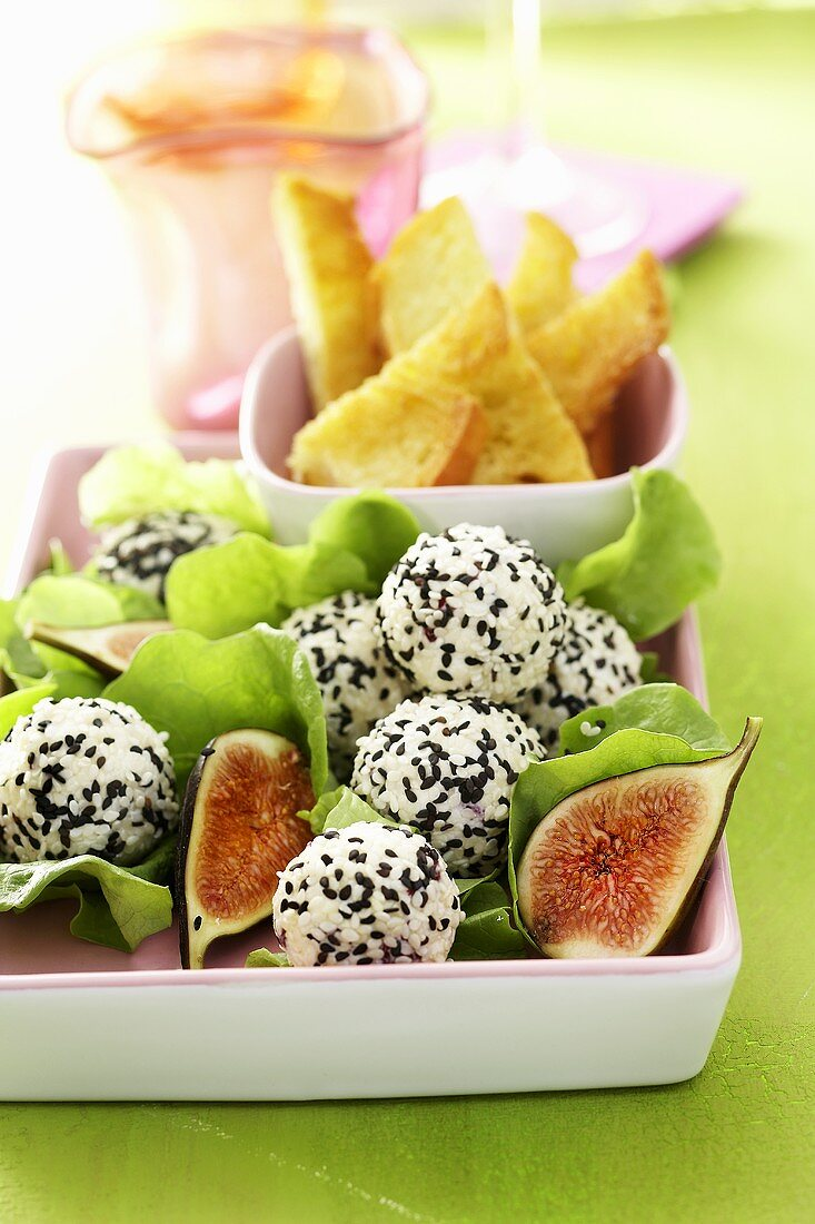 Soft cheese balls rolled in sesame seeds with figs & toast