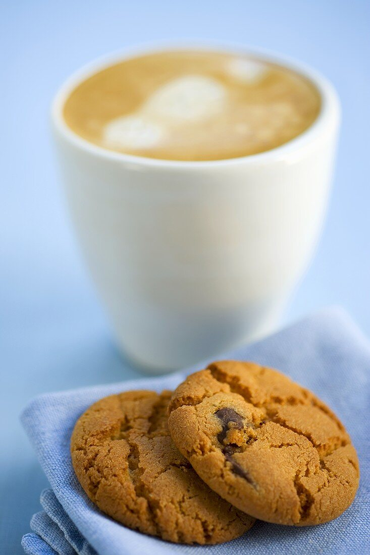 Chocolate chip biscuits and coffee with milk froth