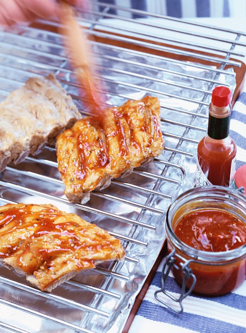 Brushing spare ribs with BBQ sauce