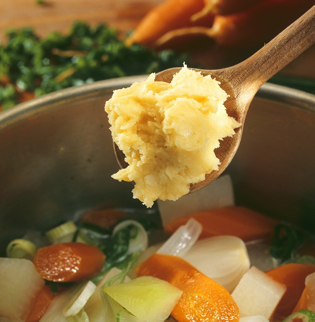 Stirring beurre manié into vegetable stew with wooden spoon