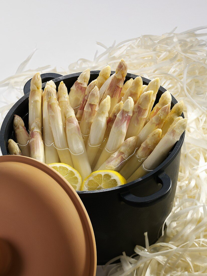 Peeled asparagus in pan with lemon slices and water