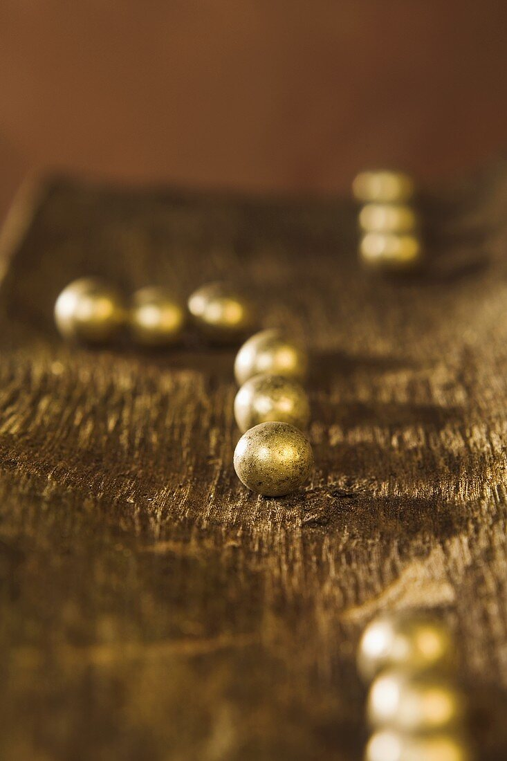 Gold-coated chocolate balls on a piece of tree bark