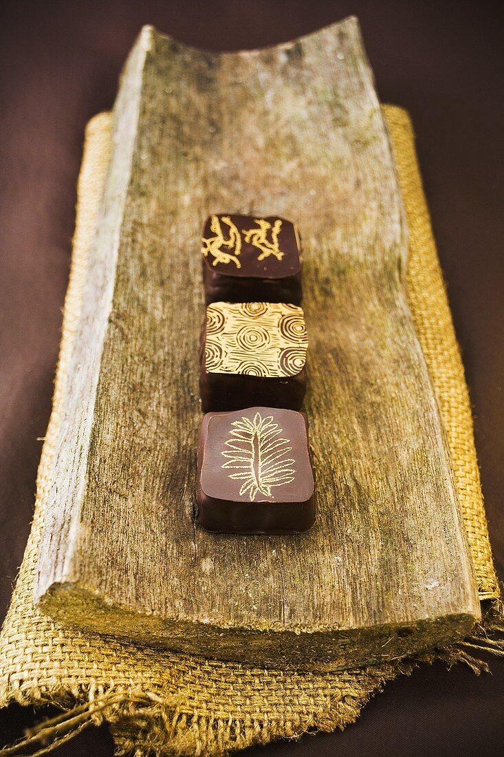 Three chocolates on a piece of tree bark