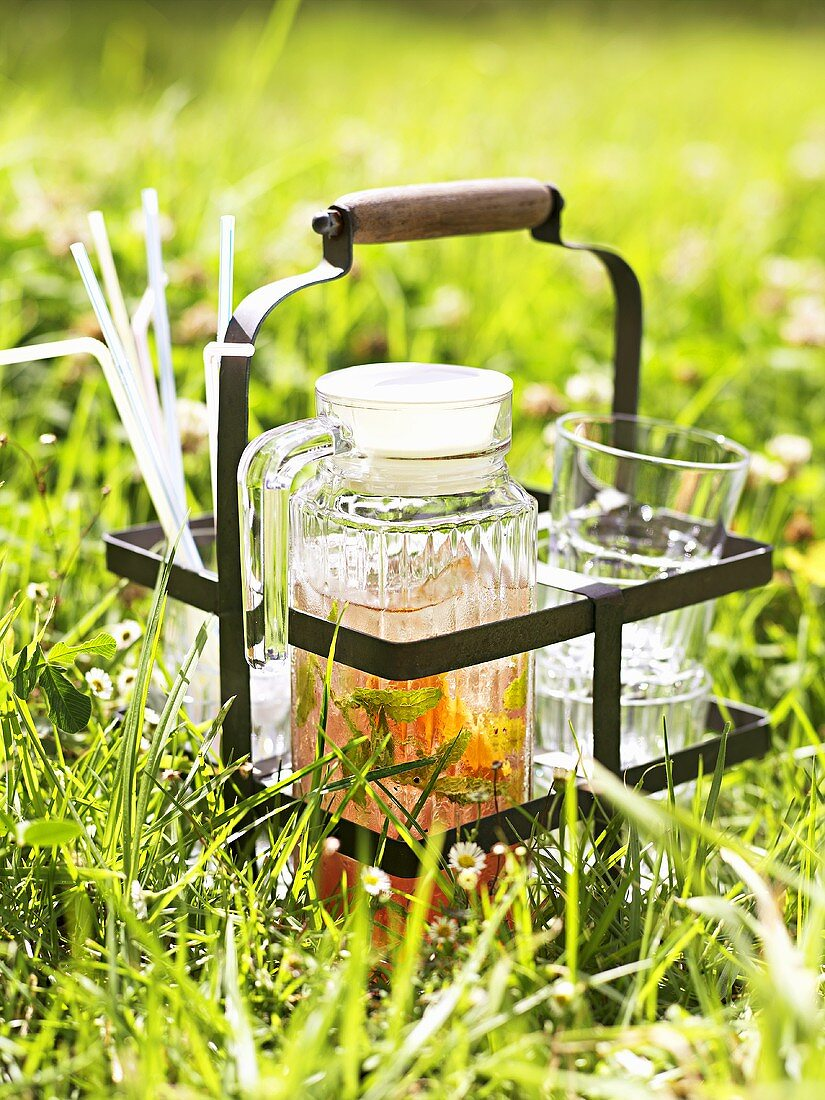 A jug of iced tea and glasses in the open air