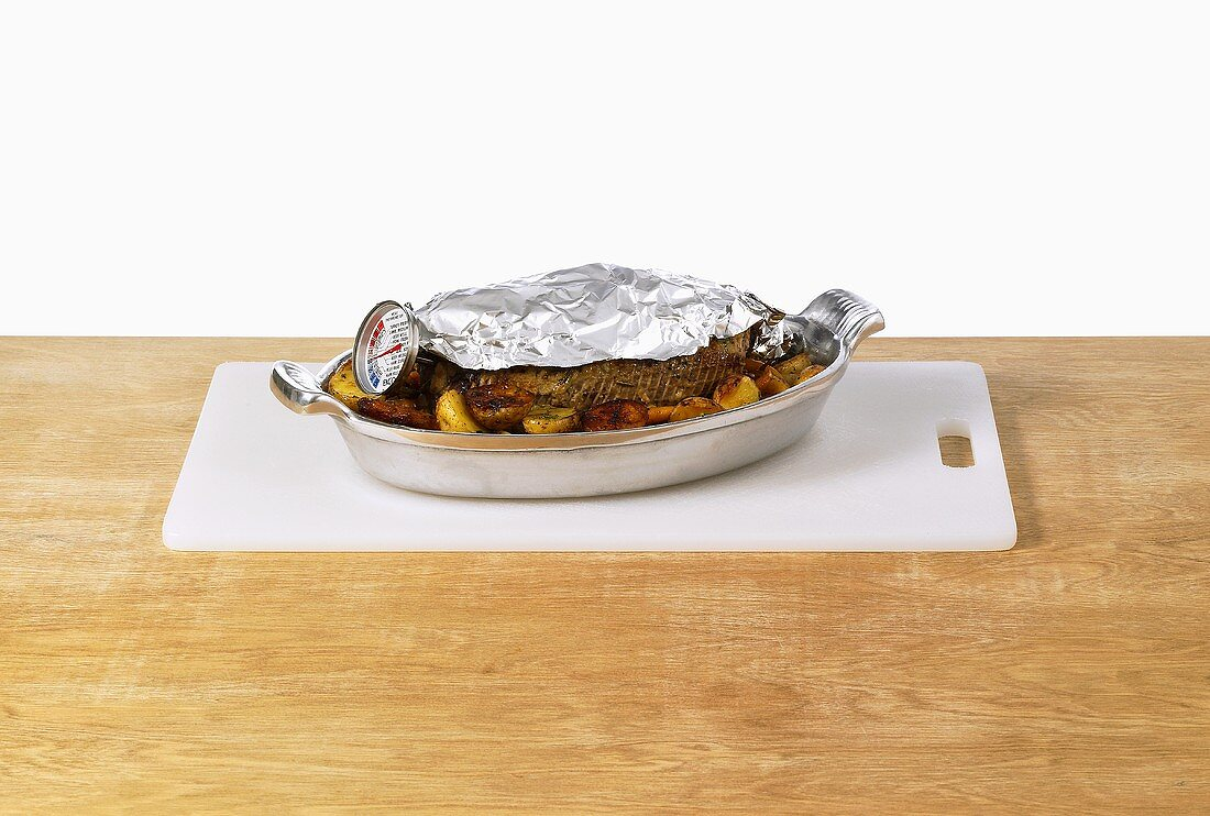 Joint with meat thermometer, partly covered with foil