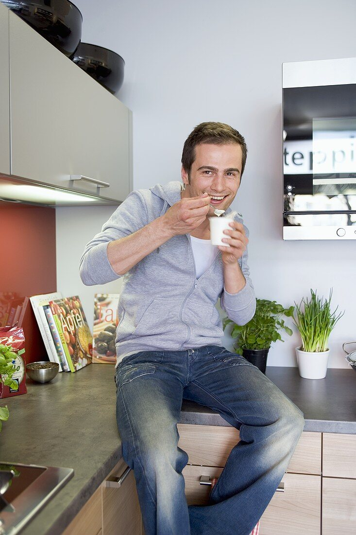 Young man sitting on work surface eating yoghurt