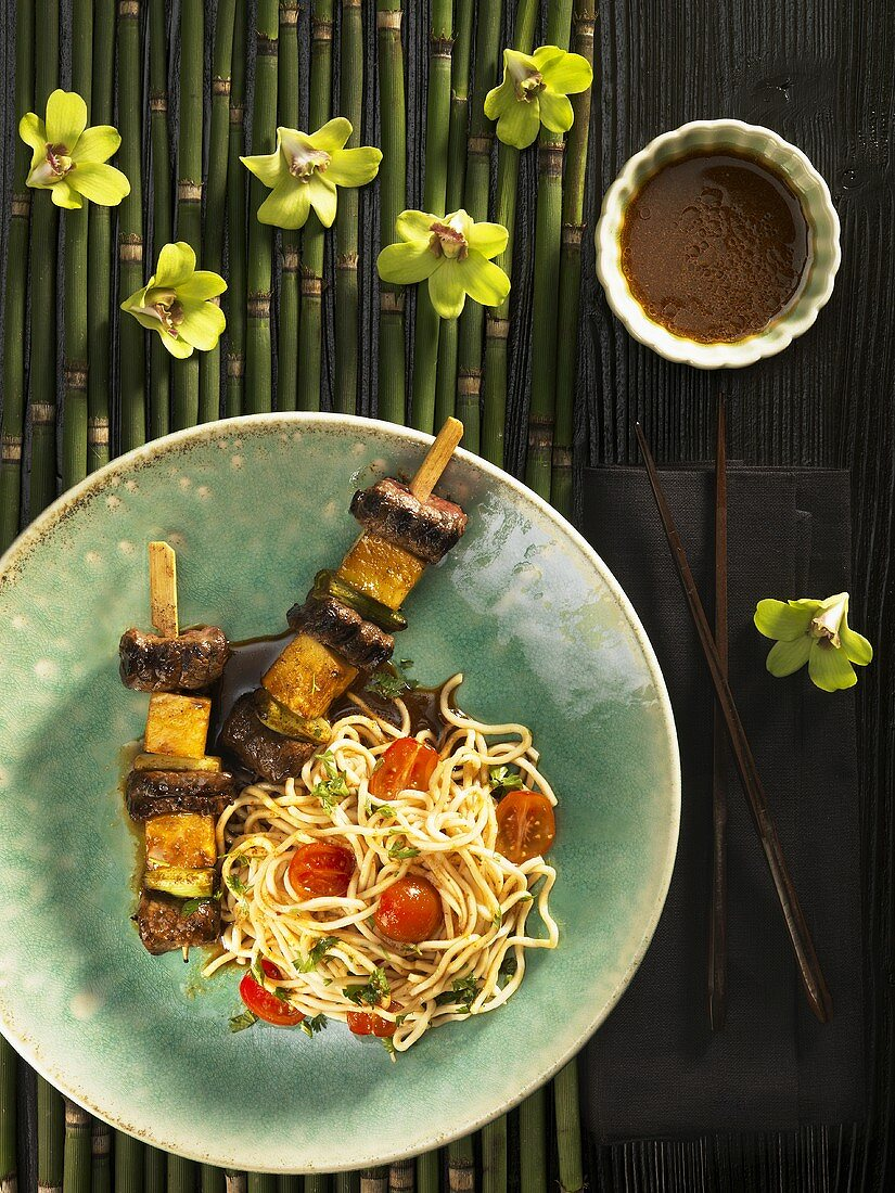Beef and pineapple skewers with noodles and tomatoes