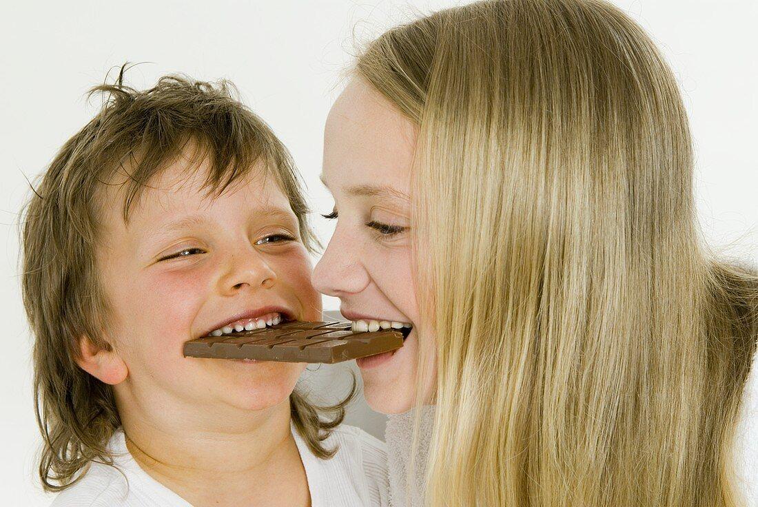 Boy and girl biting into the same bar of chocolate