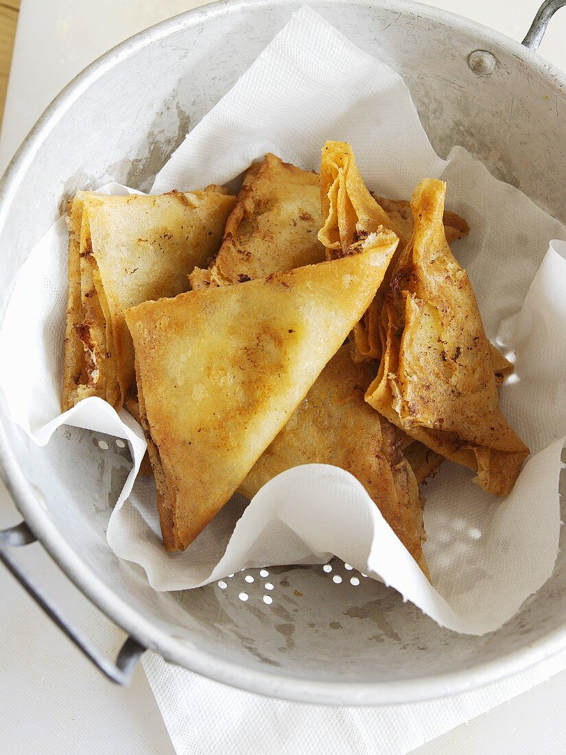 Filo pastries with potato filling, draining on paper