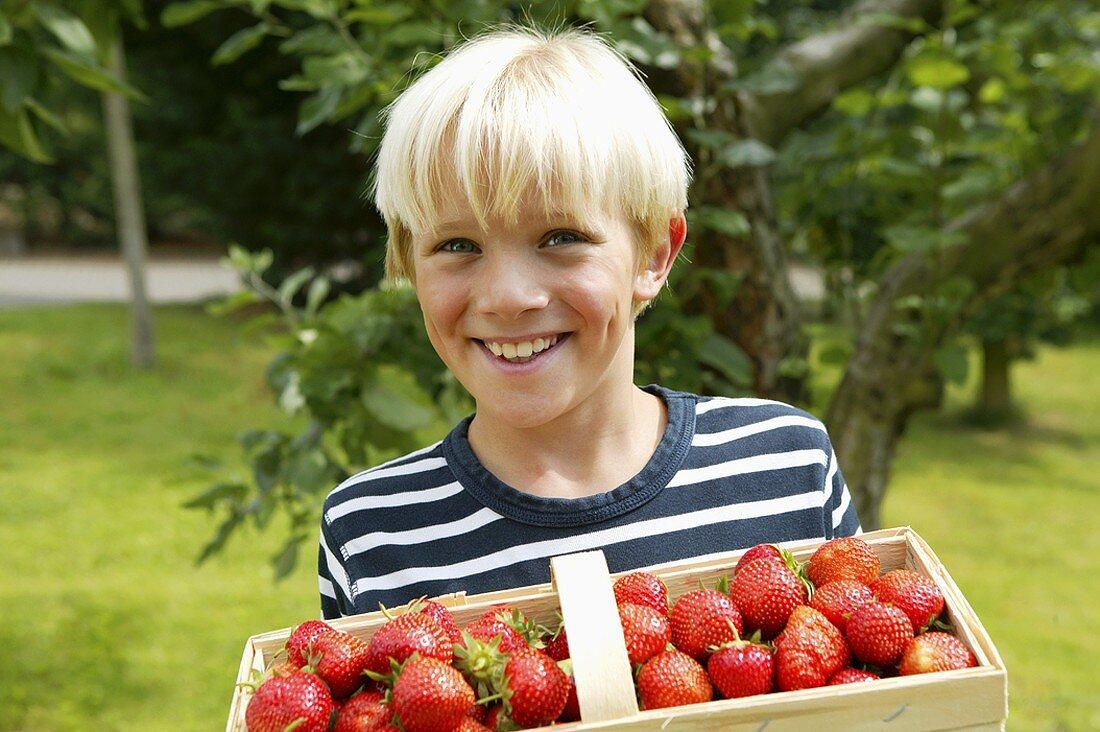 Blond boy with basket of strawberries in garden