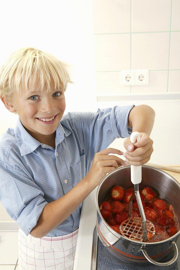 Blond boy crushing strawberries with a potato masher