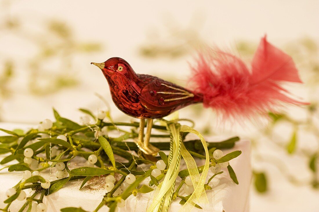 Red glass bird on a parcel decorated with mistletoe