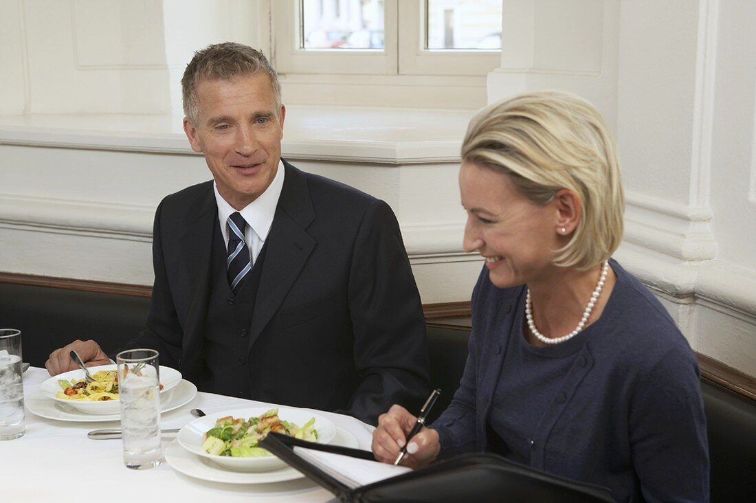 Two business partners having a discussion over a meal