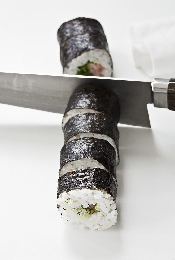 Maki sushi being cut into individual portions