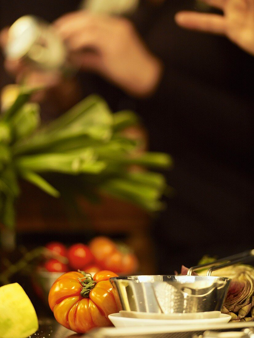 Still life with vegetables, person in background preparing food