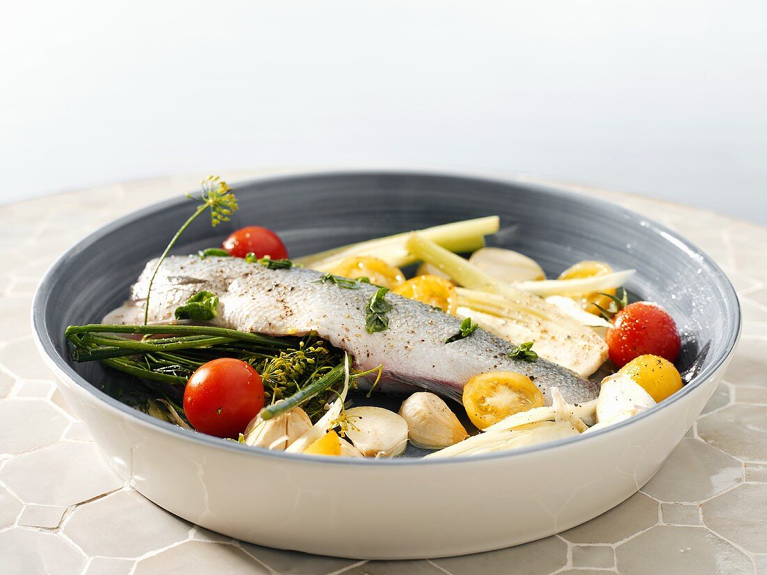 Stuffed fish with garlic and vegetables in a baking dish