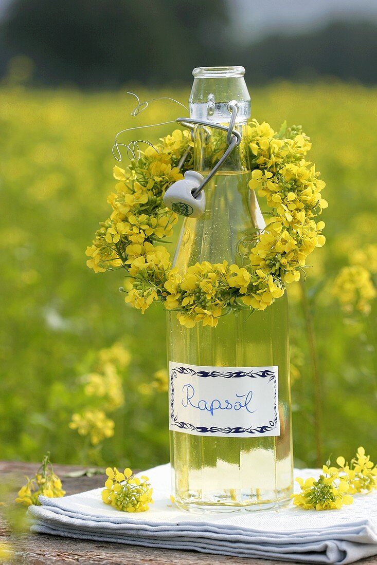 A bottle of rapeseed oil with small flower wreath
