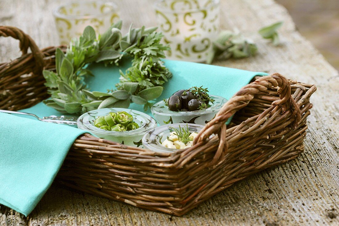 Antipasti and wreath of sage and wormwood in a basket