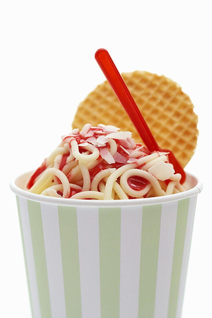 Ice cream spaghetti in tub with wafer and plastic spoon