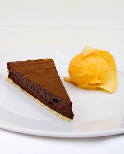 A piece of chocolate tart with mandarin orange sorbet