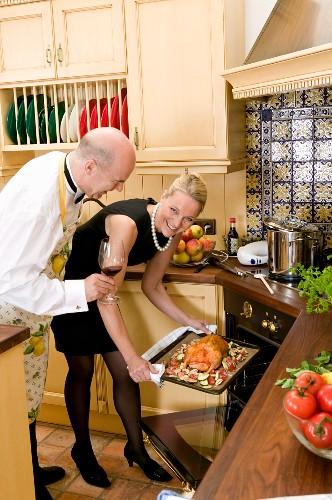 Frau schiebt Ente in den Ofen, daneben Mann mit Rotweinglas
