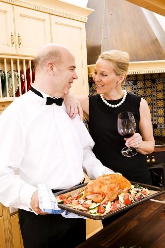 Festlich gekleidetes Paar mit vorbereitetem Entenbraten
