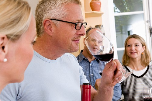 Man tasting red wine while cooking
