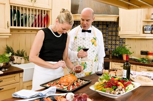 Festlich gekleidetes Paar bereitet Entenbraten zu