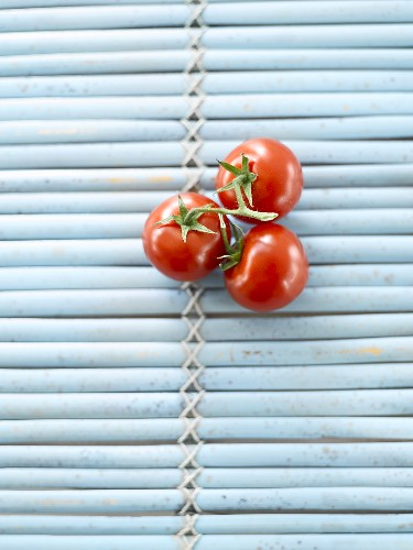 Three tomatoes on blue mat